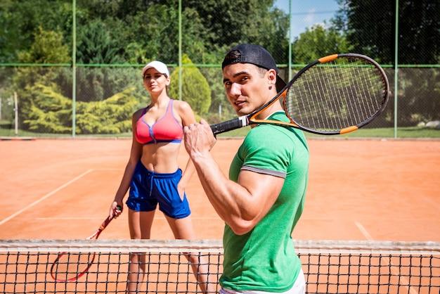 Junge athletische frau, die tennis mit ihrem trainer spielt