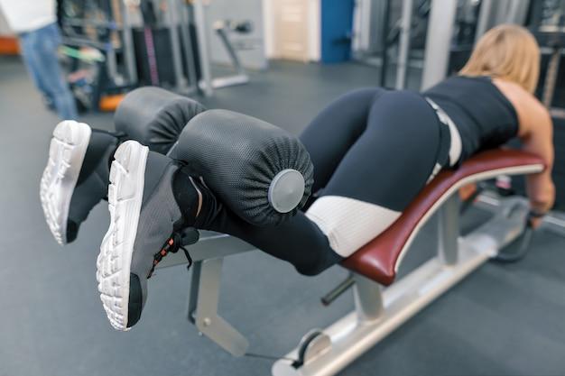 Junge athletische frau, die übungen auf beinen tut