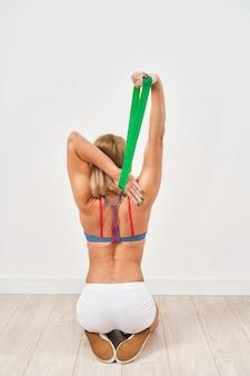 Junge athletische frau, die übungen mit fitnessgummiband tut