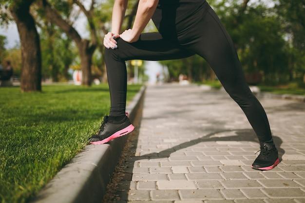 Junge athletische frau in schwarzer uniform, die sportdehnungsübungen macht, sich vor dem laufen oder training aufwärmt, im stadtpark im freien steht