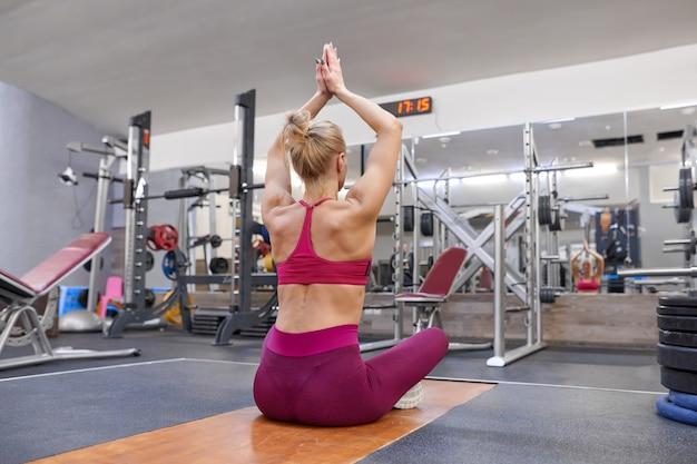 Junge athletische muskulöse frau, die training ausdehnend tut