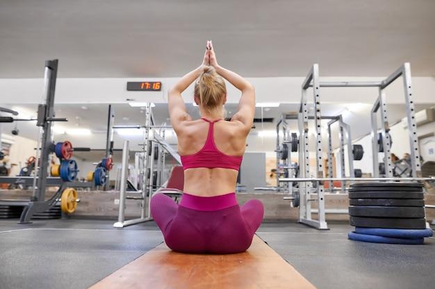 Junge athletische muskulöse frau, die training in der turnhalle ausdehnend tut