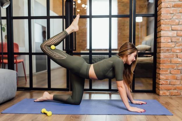 Junge athletische sportliche schlanke frau macht yoga-übungen und streckt ihr bein mit hantel zu hause