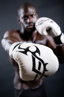 Junge athletischen boxer tragen handschuhe in schwarzem hintergrund.