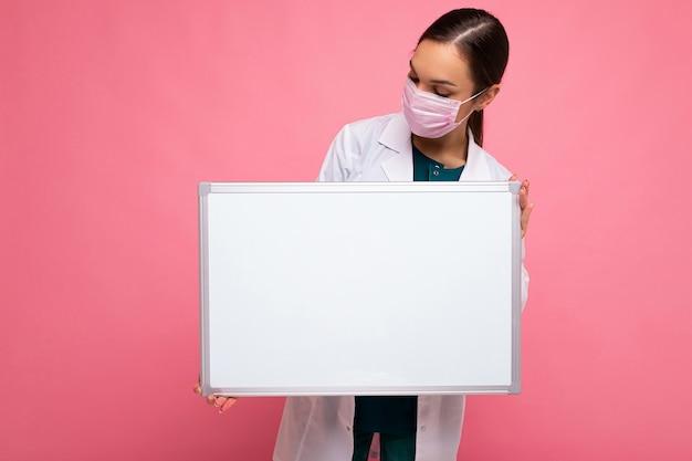 Junge attraktive ärztin in schützender gesichtsmaske und weißem medizinischem kittel, die eine leere hält