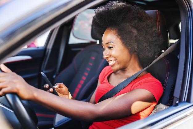 Junge attraktive afrikanische frau, die ihr auto fährt und smartphone betrachtet.