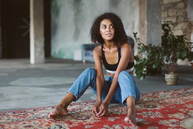 Junge attraktive afroamerikanerfrau mit dunklem lockigem haar in sportlichem oberteil und jeans, die verträumt beiseite schauen, während sie auf vintage-teppich zu hause sitzen
