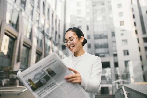 Junge attraktive asiatische bankierin oder buchhalterin in gläsern liest zeitung außerhalb eines modernen bürozentrums oder einer bank