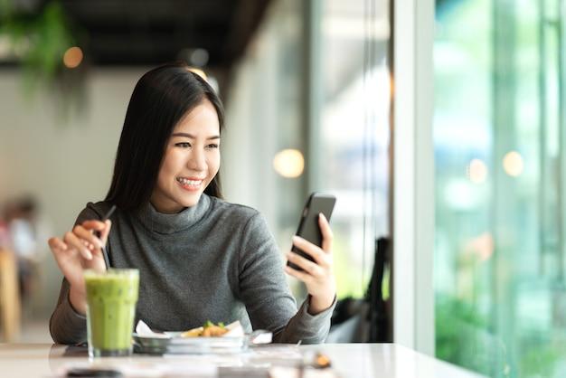 Junge attraktive asiatische frau, die in der app des handys lächelt, simst und sendet
