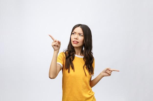 Junge attraktive asiatische frau, die mit unglücklicher emotion auf den finger zeigt