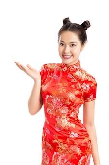 Junge attraktive asiatische frau, die rotes chinessartkleid lokalisiert trägt