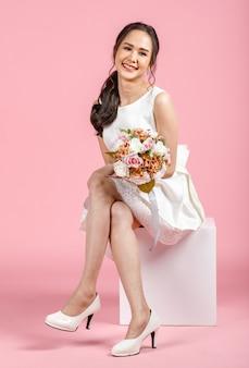 Junge attraktive asiatische frau, die weißes hochzeitskleid trägt, das sich hinsetzt und blumenstrauß gegen rosa hintergrund hält. konzept für die fotografie vor der hochzeit.