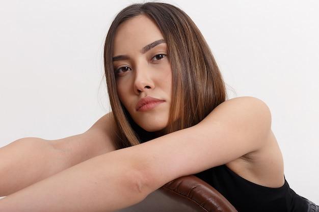 Junge attraktive asiatische frau mit langen braunen haaren, lokalisiert auf weißer wand. dünne hübsche frau, die auf stuhllehne auf cyclorama lehnt. modellversuche der schönen dame, nahaufnahme
