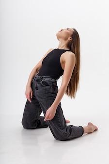 Junge attraktive asiatische frau mit langen haaren im schwarzen body, jeans, lokalisiert auf weißer wand. dünne hübsche frau auf den knien auf cyclorama stehen. modellversuche der schönen dame
