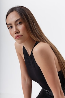Junge attraktive asiatische frau mit langen haaren im schwarzen body