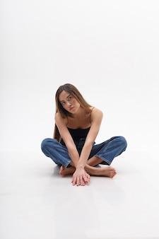 Junge attraktive asiatische frau mit langen haaren im schwarzen oberteil, blaue jeans lokalisiert auf weißer wand. dünne hübsche frau, die auf cyclorama mit gekreuzten beinen sitzt. modellversuche der schönen dame