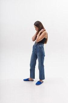 Junge attraktive asiatische frau mit langen haaren im schwarzen oberteil, blaue jeans lokalisiert auf weißer wand. dünne hübsche frau posiert auf cyclorama in flip flops. modellversuche der schönen dame