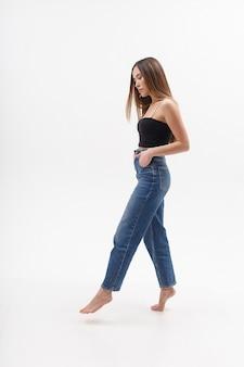 Junge attraktive asiatische frau mit langen haaren in der schwarzen spitze, blaue jeans lokalisiert auf weißem studiohintergrund. dünne hübsche frau posiert auf cyclorama mit nackten füßen. modellversuche der schönen dame