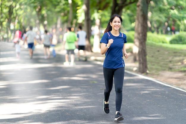 Junge attraktive asiatische läuferfrau, die in städtischen allgemeinen naturpark läuft