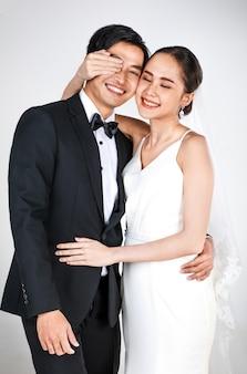 Junge attraktive asiatische paare, braut und bräutigam, frau, die weißes hochzeitskleid trägt.