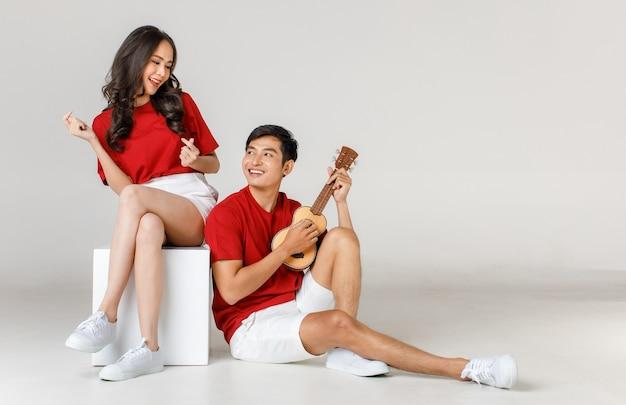 Junge attraktive asiatische paare, die rotes t-shirt und weißes kurzes sitzen tragen. mann spielt ukulele vor weißem hintergrund. konzept für die fotografie vor der hochzeit. isoliert.