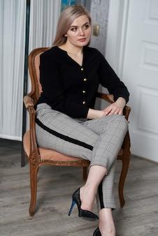 Junge attraktive blonde frau, die geschäftskleidung trägt, die auf einem stuhl sitzt