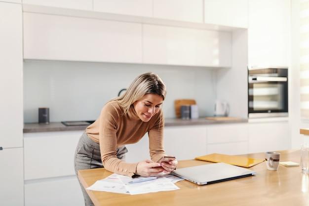 Junge attraktive blonde frau, die sich auf küchentisch stützt und smartphone für e-banking verwendet.