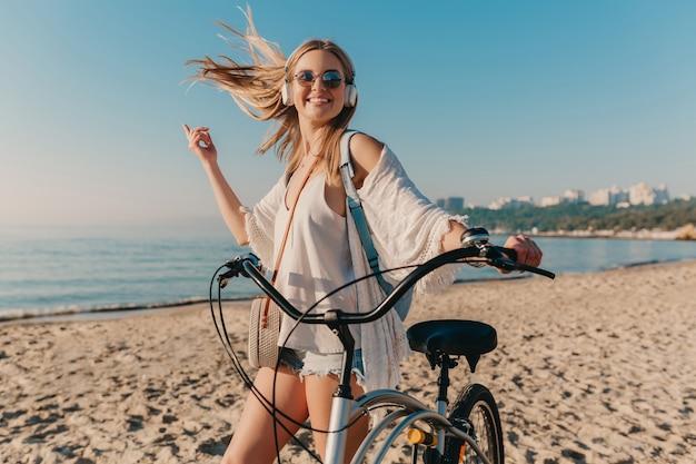 Junge attraktive blonde lächelnde frau, die am strand mit dem fahrrad in den kopfhörern geht, die musik hören