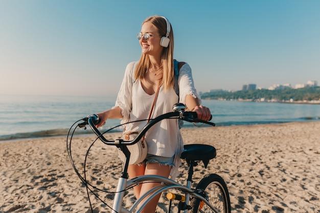 Junge attraktive blonde lächelnde frau, die am strand mit dem fahrrad in den kopfhörern geht