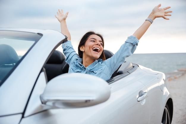 Junge attraktive brünette frau, die mit ihren händen oben im cabriolet sitzt