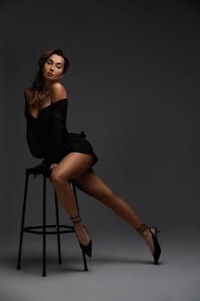 Junge attraktive brünette sexy frau sitzt auf stuhl im erotischen schwarzen cocktailkleid