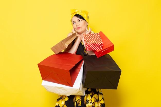 Junge attraktive dame der vorderansicht im gelb-schwarzen blumenentwurfskleid mit gelbem verband auf kopf, der einkaufspakete auf dem gelben hält