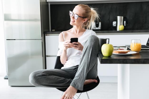 Junge attraktive dame, die bei der anwendung des smartphone beiseite schaut