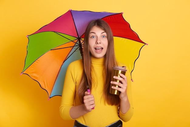 Junge attraktive dame mit erstauntem gesichtsausdruck, der mit buntem regenschirm und kaffee zum mitnehmen aufwirft, steht mit geöffnetem mund