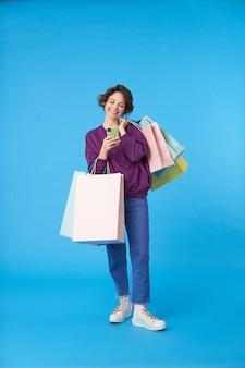 Junge attraktive dunkelhaarige frau mit kurzem haarschnitt mit vielen einkaufstaschen