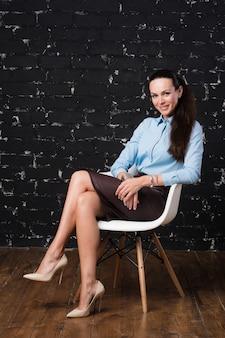 Junge, attraktive, erfolgreiche geschäftsfrau, sitzend auf einem stuhl.