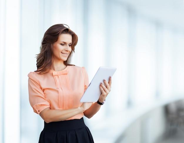 Junge, attraktive, erfolgreiche geschäftsfrau studiert den vertrag auf dem tablet.
