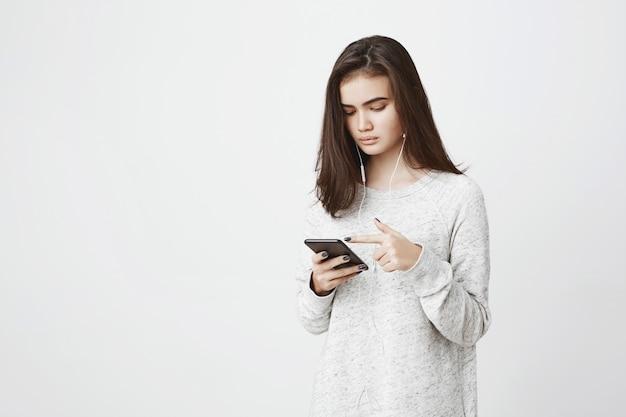 Junge attraktive europäische frau, die musik hört und nachrichtenfeed in ihrem smartphone mit konzentriertem ausdruck scrollt. frau sieht live-stream durch eine app