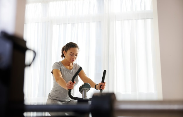 Junge attraktive fit frau konzentrierte sich auf cardio-training zu hause