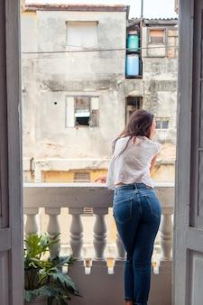 Junge attraktive frau auf altem balkon in den wohnungen in havana