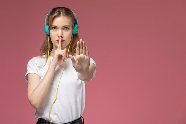 Junge attraktive frau der vorderansicht, die musik über ihre kopfhörer hört, die stillezeichen auf dem weiblichen jungen mädchen der rosa wandmodellfarbe zeigen