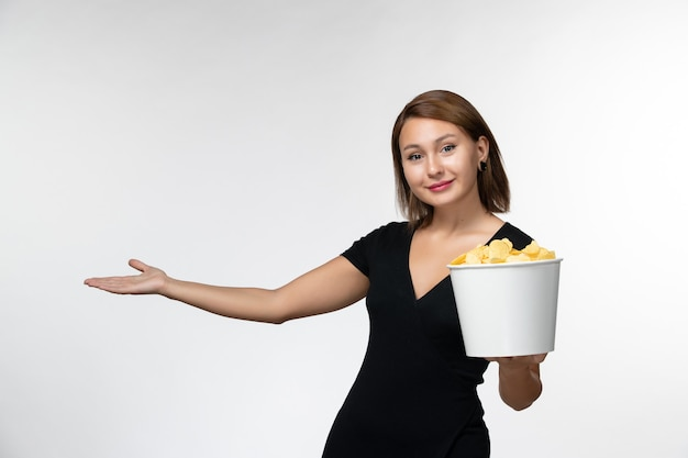 Junge attraktive frau der vorderansicht im schwarzen hemd, das kartoffelspitzen hält und auf weißer oberfläche lächelt