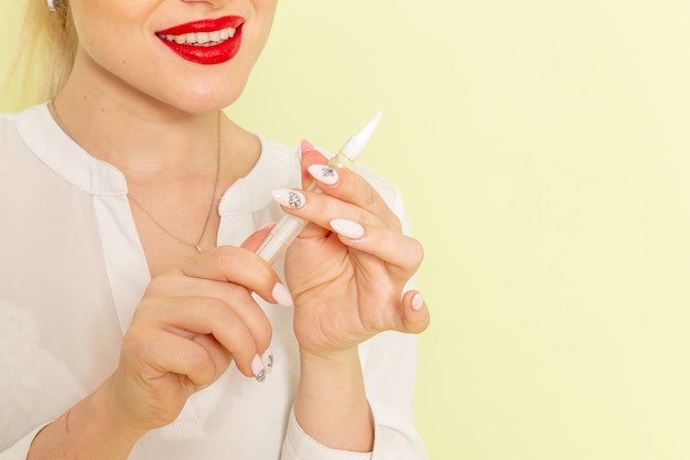 Junge attraktive frau der vorderansicht im weißen hemd, das mit ihren nägeln auf der grünen oberfläche arbeitet
