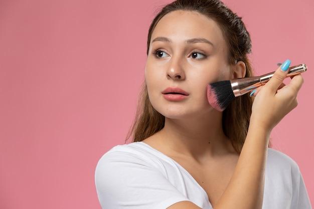 Junge attraktive frau der vorderansicht im weißen t-shirt, das make-up auf dem rosa hintergrund tut