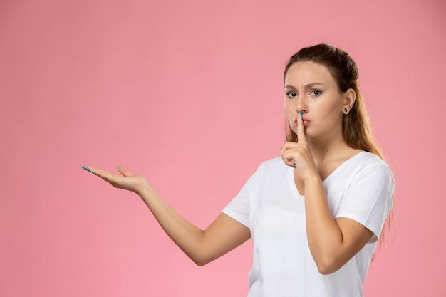 Junge attraktive frau der vorderansicht im weißen t-shirt, das schweigenzeichen auf dem rosa hintergrund zeigt