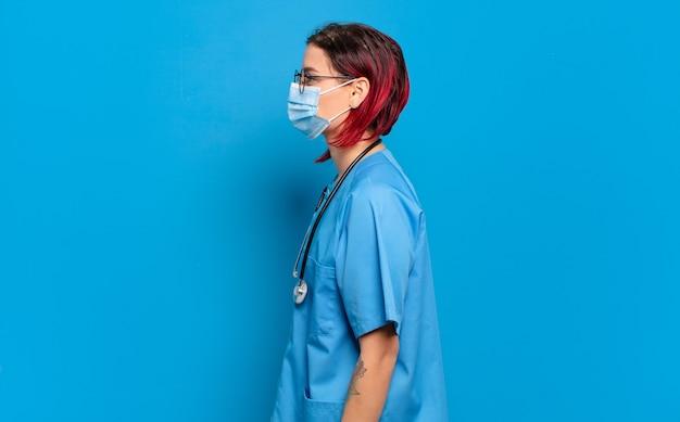 Junge attraktive frau des roten haares auf profilansicht, die raum voraus kopiert, denkt, sich vorstellt oder tagträumen. krankenhauskrankenschwester-konzept