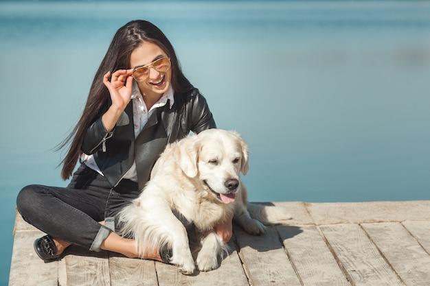 Junge attraktive frau, die am pier mit ihrem hund sitzt. beste freunde im freien