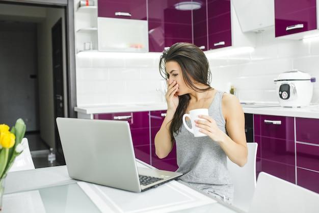 Junge attraktive frau, die an pc an der küche arbeitet. frau, die morgens am computer arbeitet. freiberufler am laptop innen.