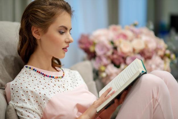 Junge attraktive frau, die auf dem sofa sitzt und ein buch liest, genießt ruhe.