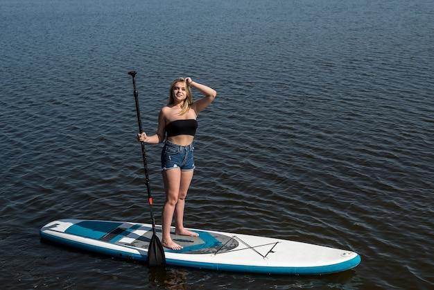 Junge attraktive frau, die auf paddelbrett aufwirft und im heißen heißen sonnentag des sommers entspannt